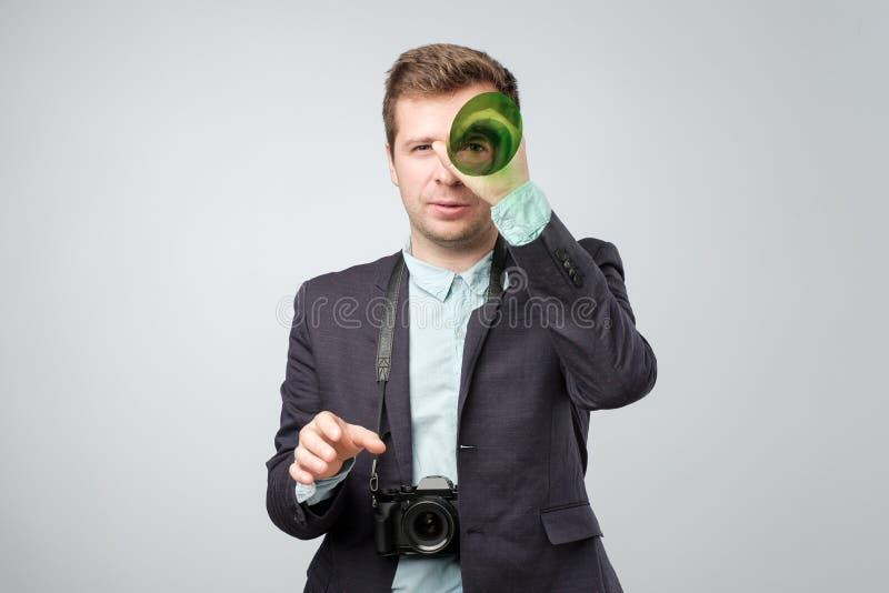 Stilig ung man som rymmer en fotokamera arkivbilder