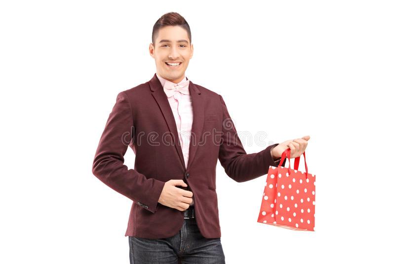 Stilig ung man som rymmer en shoppingpåse royaltyfria foton