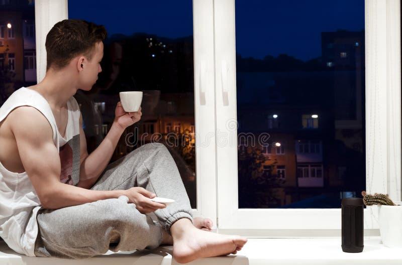 Stilig ung man som sitter nära fönster i aftonen arkivfoto