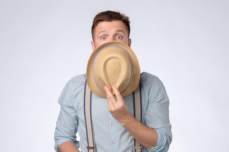 Stilig ung man som täcker framsidan med hatten som ser chockad och förbluffad arkivbilder