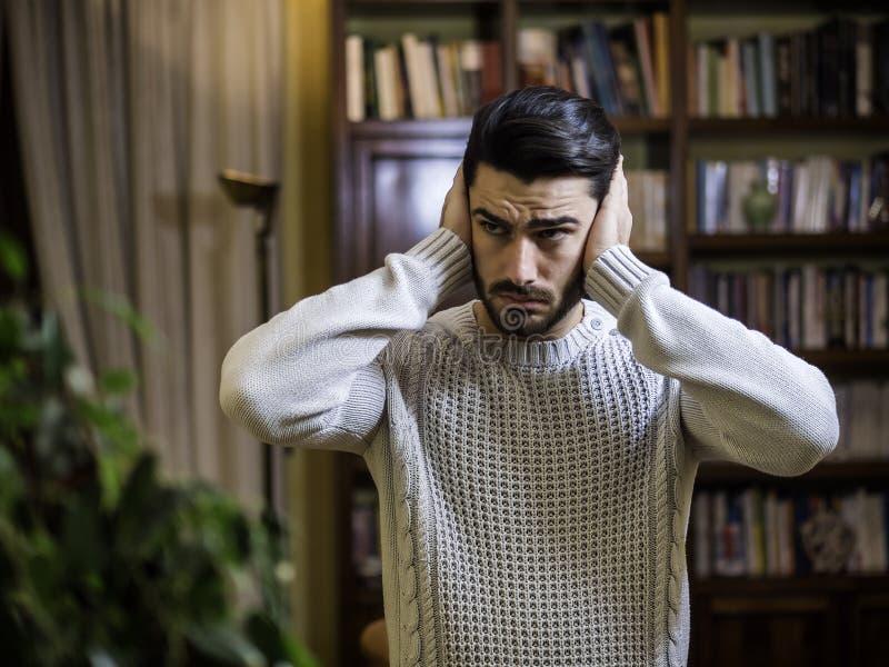 Stilig ung man som täcker hans öron, för mycket oväsen arkivbilder