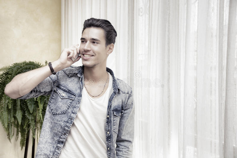 Stilig ung man som talar på hemmastatt le för telefon royaltyfria bilder