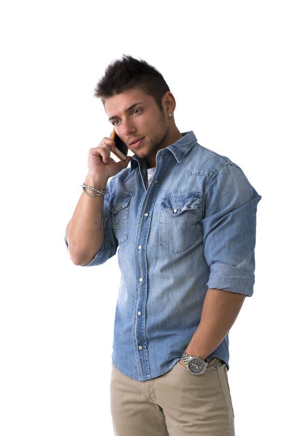 Stilig ung man som talar på mobiltelefonen (mobil) som isoleras arkivfoton