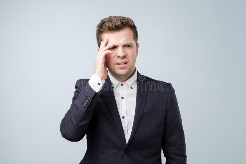 Stilig ung man som trycker på hans huvud med handen som känner stark huvudvärk royaltyfri bild