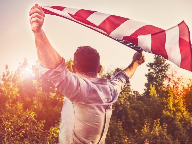 Stilig ung man som vinkar en amerikanska flaggan fotografering för bildbyråer