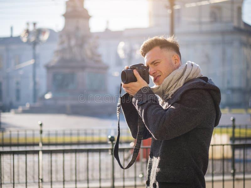 Stilig ung manlig fotograf som tar det utomhus- fotografiet arkivbild