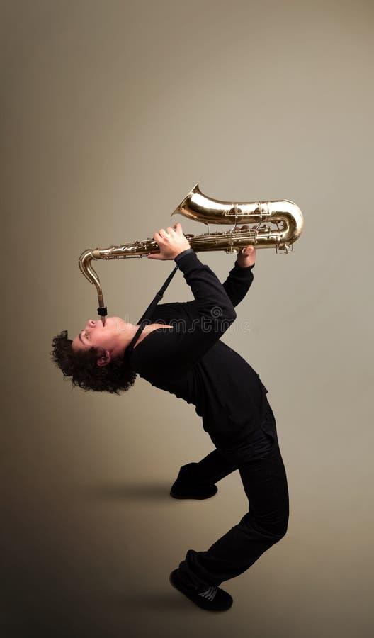 Ung musiker som leker på saxofon arkivbilder