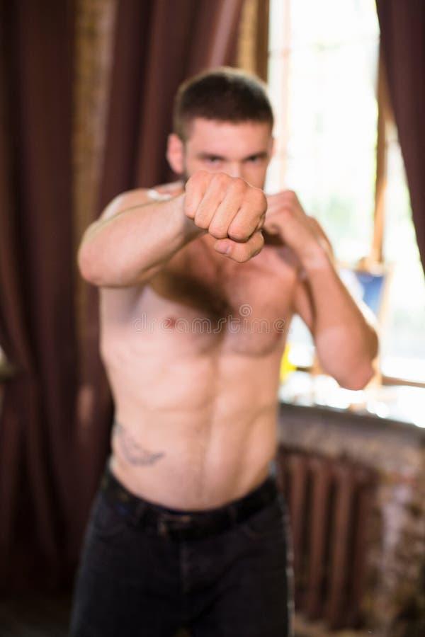 Stilig ung muskulös manboxning i hemmiljö arkivbilder