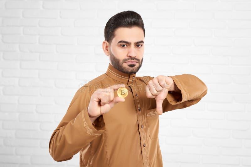Stilig ung muslimsk man som är ledsna och förargade hållande guld- bitcoin- och visningtummar ner fotografering för bildbyråer