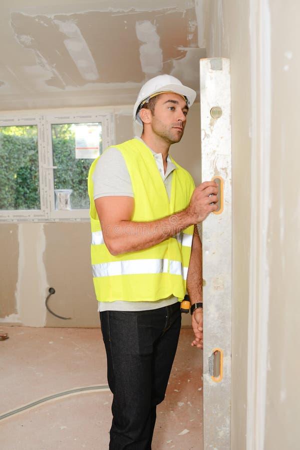 Stilig ung ordförande som övervakar en plats för husrenoveringcontruction royaltyfri fotografi
