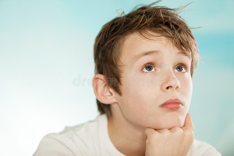Stilig ung tonårs- pojke som är borttappad i tanke arkivfoton