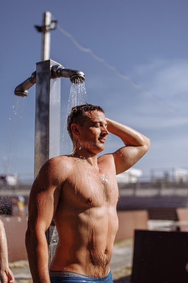 Stilig ung topless caucasian man som tar en utomhus- dusch på stranden arkivbilder
