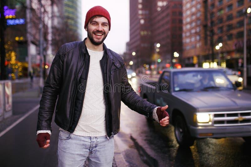 Stilig ung turist som liftar på vägen Låsbil på huvudvägen Turism och folkbegrepp aktiv livsstil royaltyfri foto