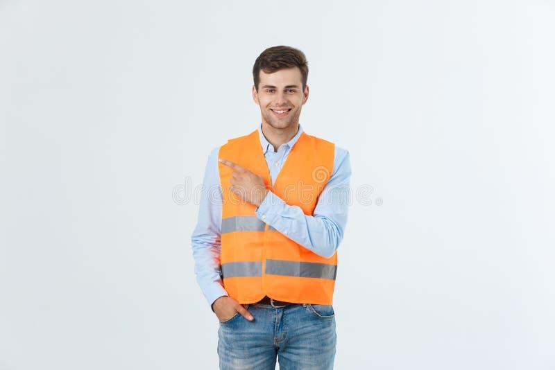 Stilig ung yrkesmässig teknikerman över den gråa väggen som bär orange förbluffat och förvånat se för väst och peka arkivfoton