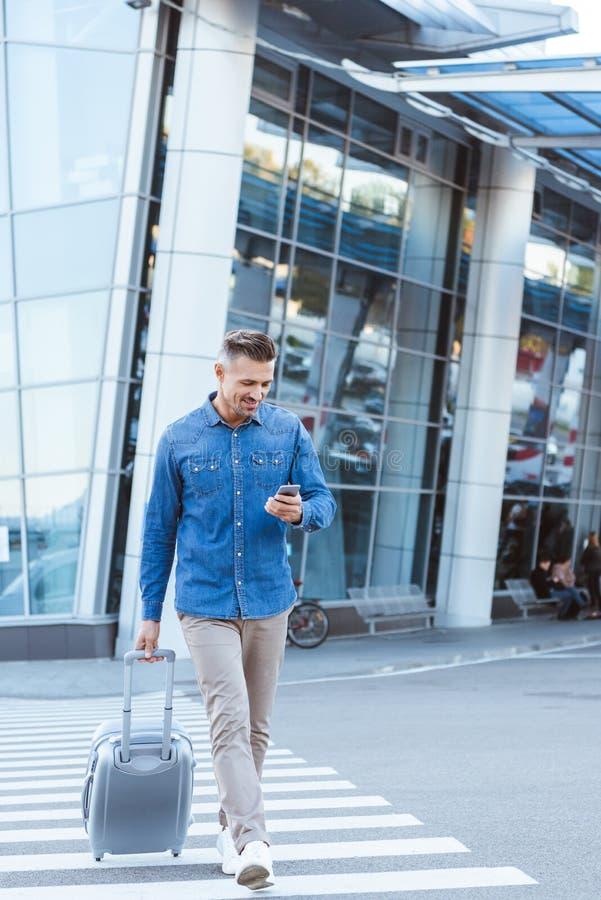 Stilig vuxen man med bagage som korsar gångaren som ser in i smartphonen på bakgrunden arkivbilder