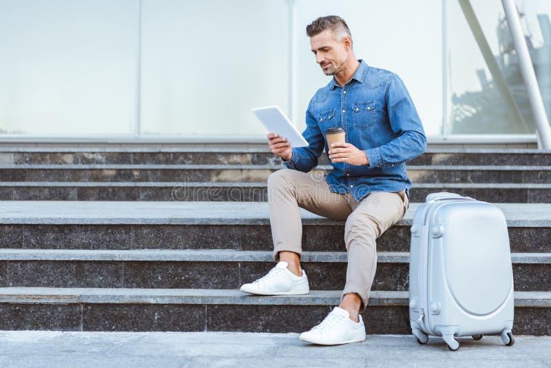 Stilig vuxen man med ett kaffe som går sitta på trappuppgången med bagage och royaltyfria bilder
