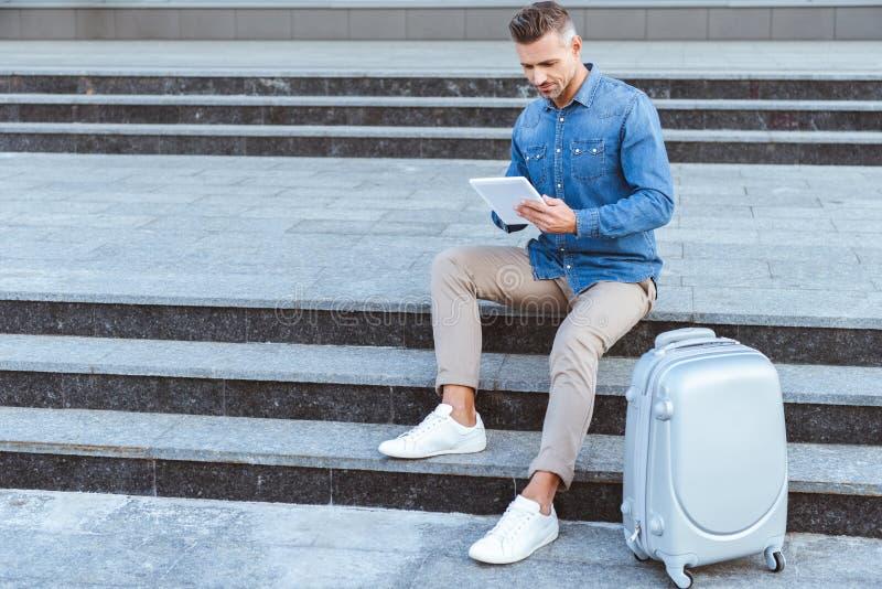 Stilig vuxen man som sitter på trappuppgången med bagage och royaltyfria bilder