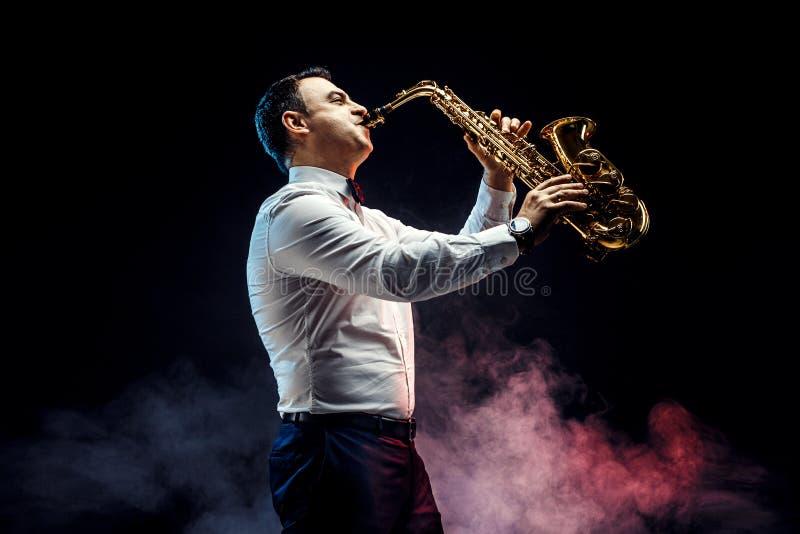 Stilig vuxen man som spelar saxofonen arkivbilder