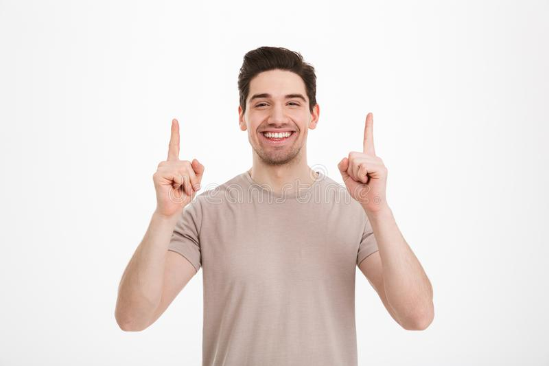 Stilig vuxen man30-tal som bär den beigea t-skjortan som framlägger copyspac arkivbild