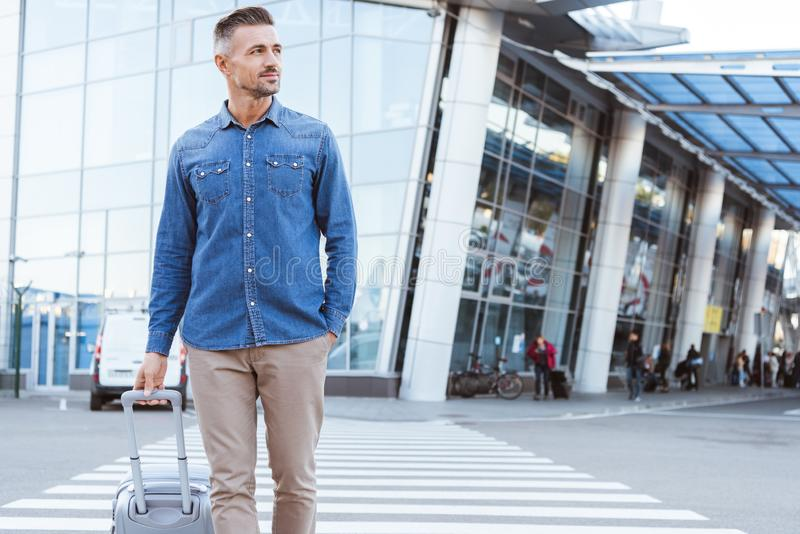 Stilig vuxen mankorsning gångare och att dra hans bagage, bort se och le på bakgrunden royaltyfri bild