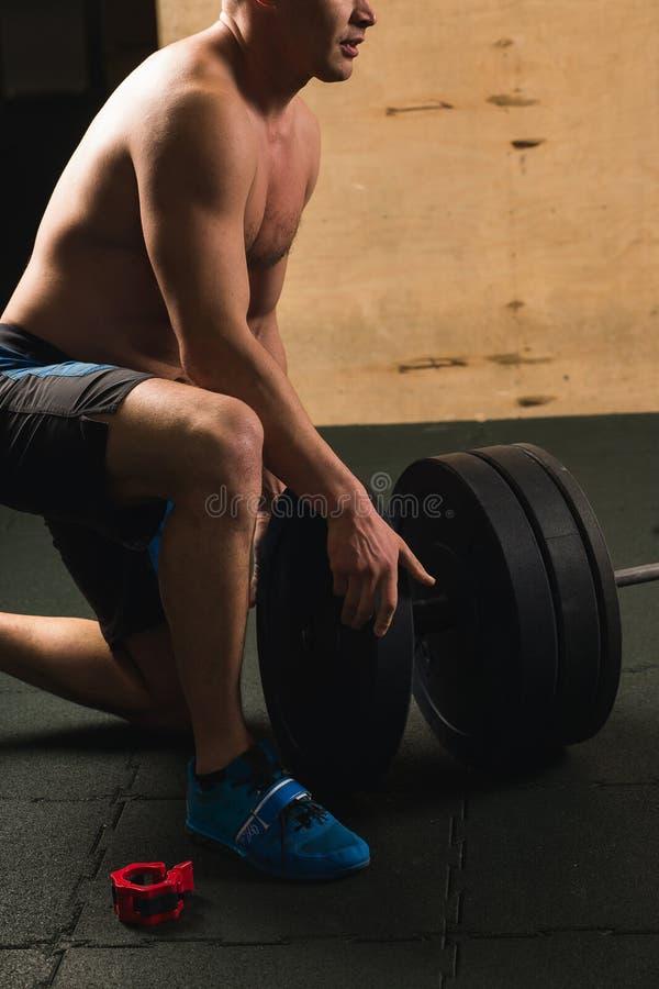 Stilig weightlifter som förbereder sig för utbildning med skivstången royaltyfri foto