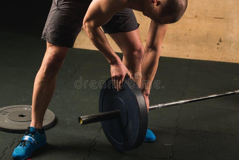 Stilig weightlifter som förbereder sig för utbildning med skivstången royaltyfria foton