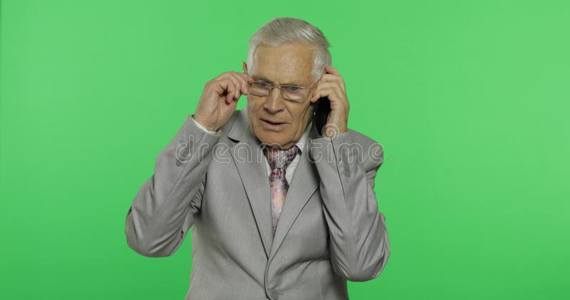 Stiliga äldre affärsmansamtal på en smartphone Gamal man i dräkt royaltyfri bild
