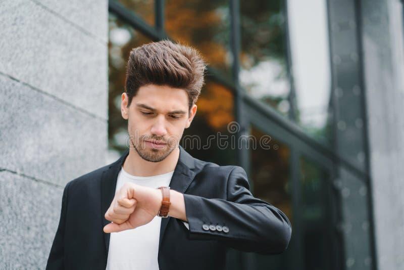 Stiliga affärsman- eller studentblickar på klockan Ung man i brådska sent för arbete Manlig modell på kontorsbyggnad arkivfoton