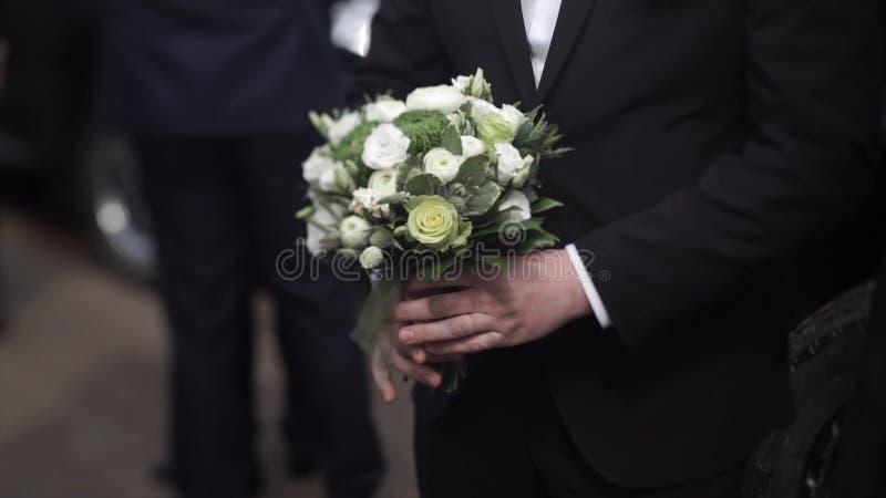 Stiliga affärsmaninnehavblommor Ansa i en dräkt som rymmer en bukett av blommor Bröllopboutonniere elegant man arkivbilder