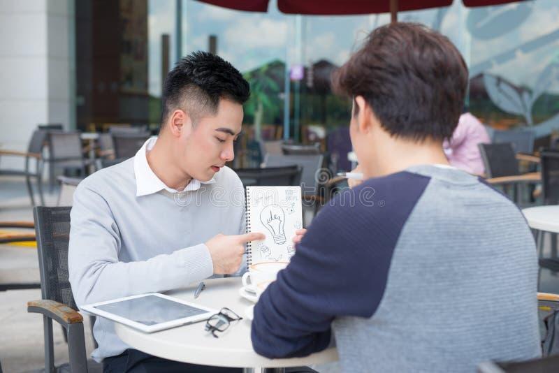 Stiliga asiatiska affärskollegor eller högskolestudenter arbetar toge arkivbilder