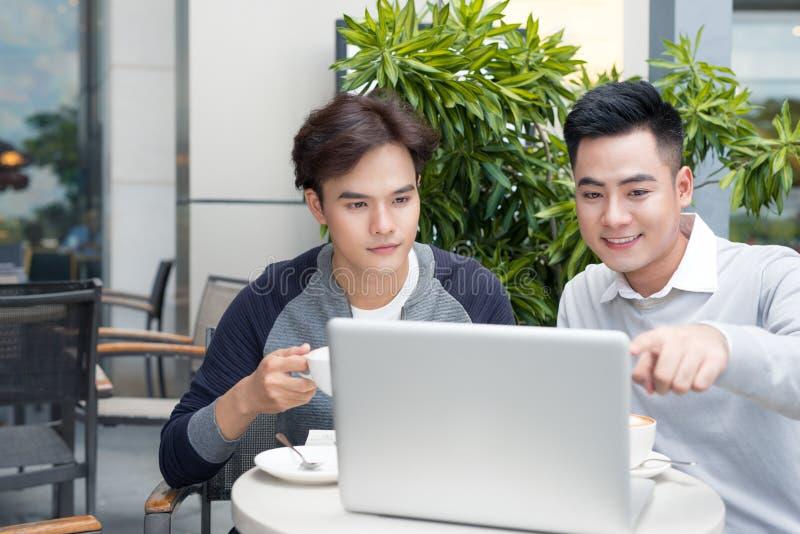 Stiliga asiatiska affärskollegor eller högskolestudenter arbetar toge fotografering för bildbyråer