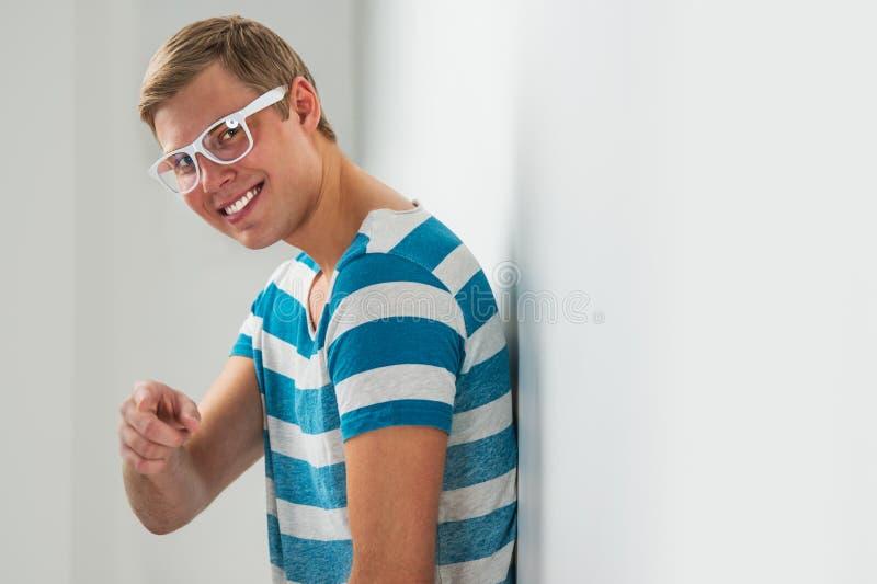 Stiliga bärande exponeringsglas för ung man som lutar på väggen royaltyfria bilder