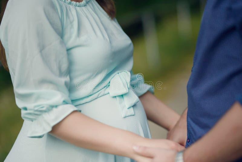 Stiliga Caucasian par som rymmer h?nder med fokusen p? gravida kvinnans h?rliga runda, behandla som ett barn bulan arkivbild