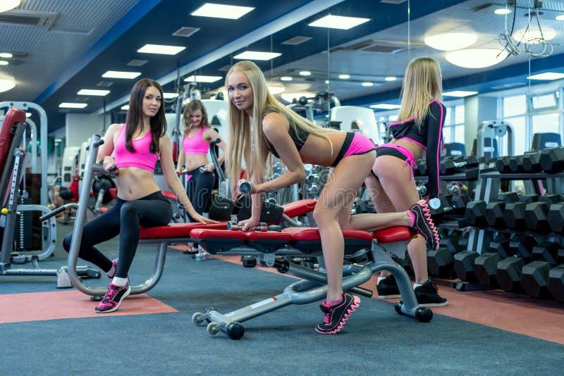 Stiliga flickor som poserar, medan öva i idrottshall arkivfoton
