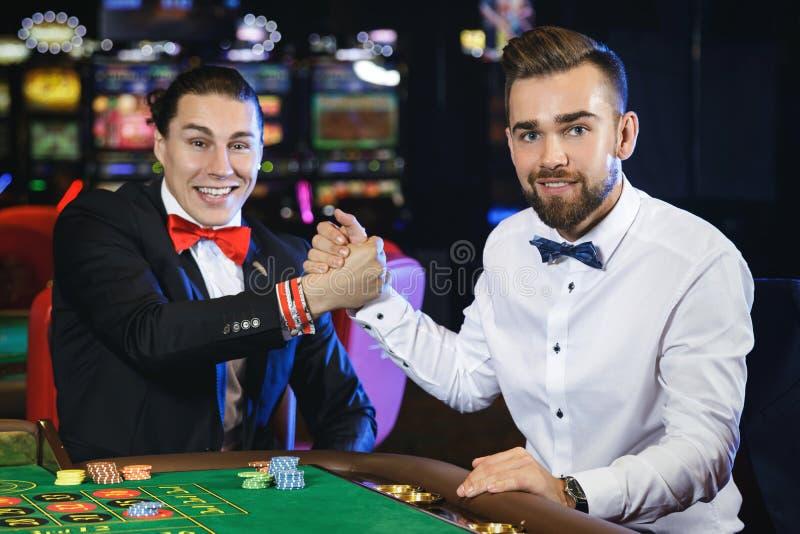 Stiliga grabbar som spelar rouletten i kasinot arkivbilder