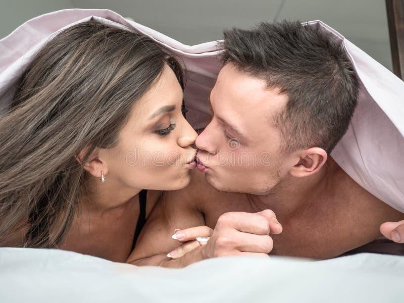 Stiliga kyssande par under ett duntäcke i sängen Det lyckliga barnet kopplar ihop att ligga ner bekvämt i deras säng hemma Barn royaltyfria bilder