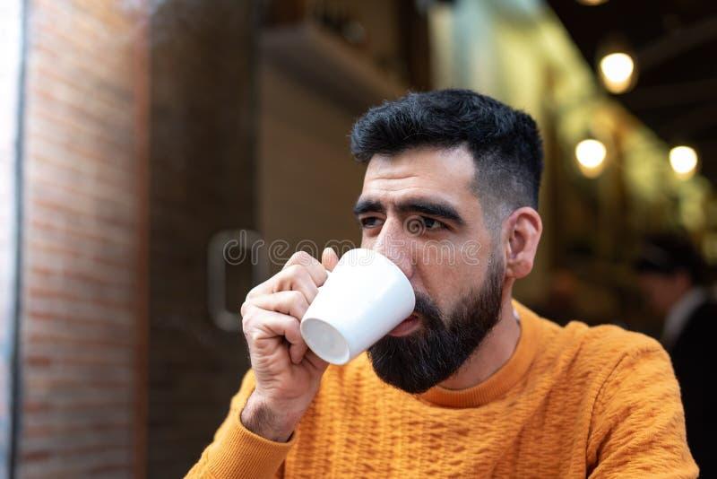 Stiliga latinska Guy Drinking Coffee i ett terrasskafé fotografering för bildbyråer