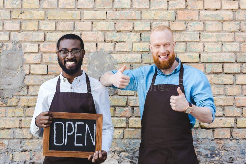 stiliga multietniska ägare av coffee shop i förkläden som rymmer tecknet öppet och visar tummar upp att le royaltyfri bild