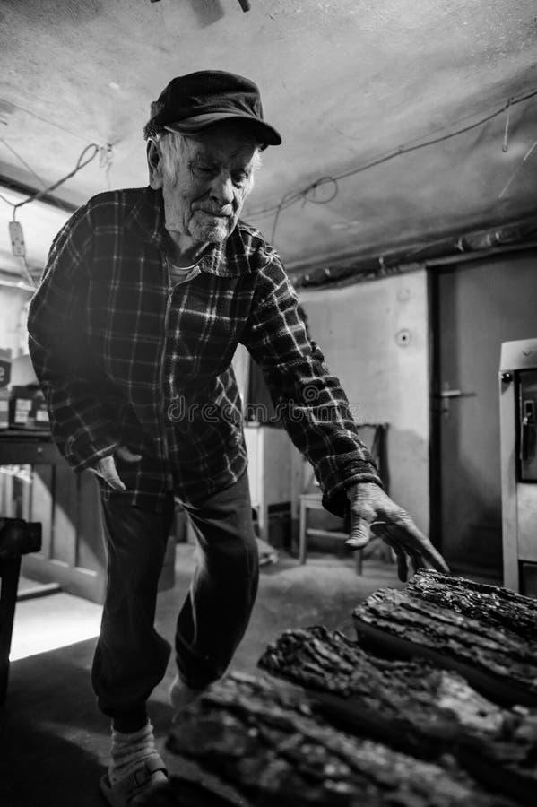 Stiliga 80 plus den åriga ståenden för hög man Svartvit full kroppbild av den äldre mannen i kokkärlrum som startar brand arkivbild