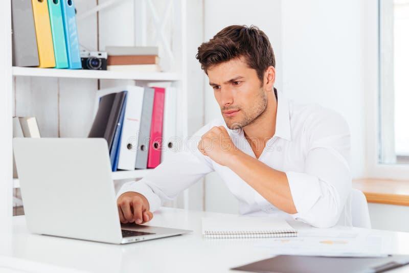 Stiligt affärsmansammanträde på skrivbordet och användabärbara datorn fotografering för bildbyråer