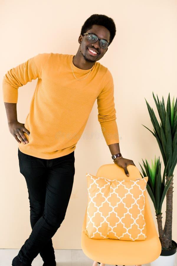 Stiligt anseende för svart grabb nära den gula stolen över ljust - gul bakgrund arkivfoto