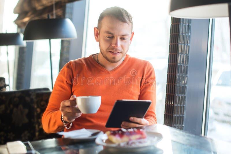 Stiligt arbete för ung man som ser in i minnestavlan, medan tycka om kaffe i kafé royaltyfri bild