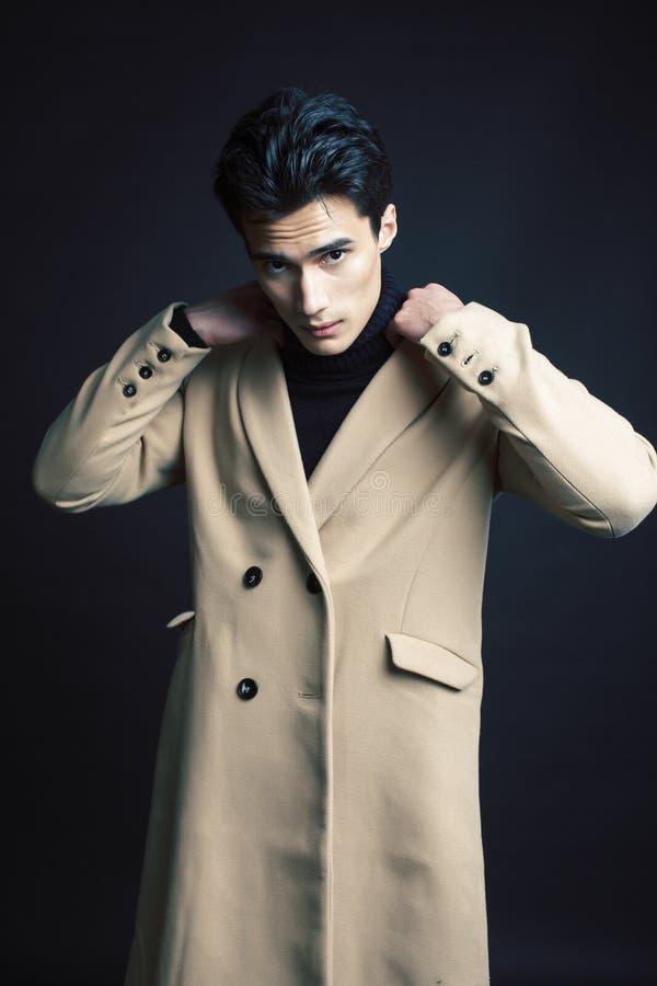 Stiligt asiatiskt mode som ser mannen som poserar i studio p? svart bakgrund, f?r folkbegrepp f?r livsstil modernt slut upp royaltyfri foto