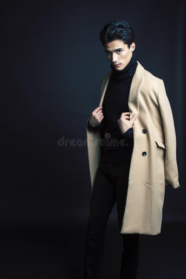 Stiligt asiatiskt mode som ser mannen som poserar i studio p? svart bakgrund, f?r folkbegrepp f?r livsstil modernt slut upp fotografering för bildbyråer