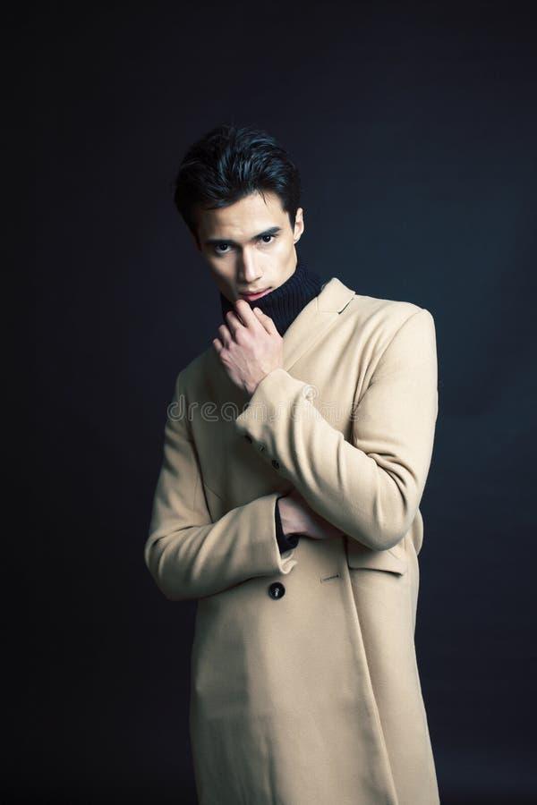 Stiligt asiatiskt mode som ser mannen som poserar i studio p? svart bakgrund, f?r folkbegrepp f?r livsstil modernt slut upp arkivfoto