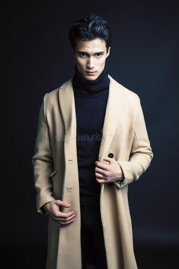 Stiligt asiatiskt mode som ser mannen som poserar i studio p? svart bakgrund, f?r folkbegrepp f?r livsstil modernt slut upp arkivfoton