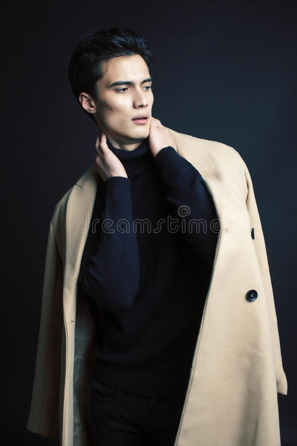 Stiligt asiatiskt mode som ser mannen som poserar i studio p? svart bakgrund, modernt folkbegrepp f?r livsstil arkivbild