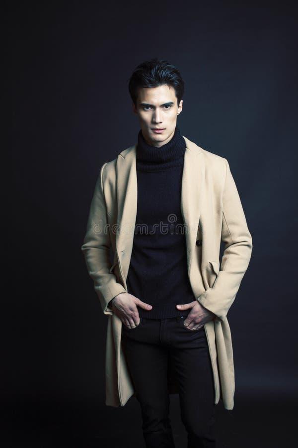 Stiligt asiatiskt mode som ser mannen som poserar i studio p? svart bakgrund, modernt folkbegrepp f?r livsstil arkivbilder