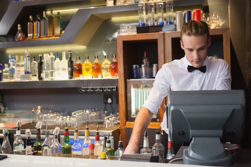 Stiligt bartenderanseende på kassaapparaten arkivfoto
