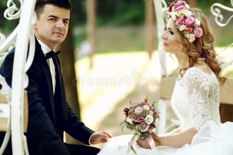 Stiligt brudgumsammanträde med den blonda härliga bruden i magisk fa royaltyfria bilder